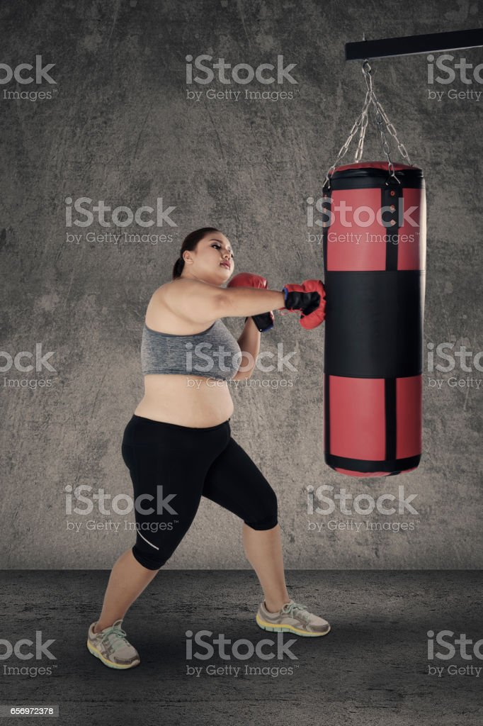 Obese woman punching a boxing bag stock photo