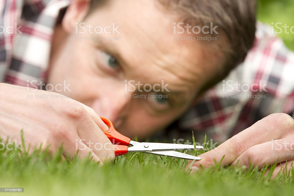 Obsessive man laying on grass, perfection stock photo