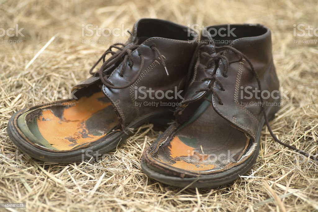 obsolete old shoes on straw stock photo