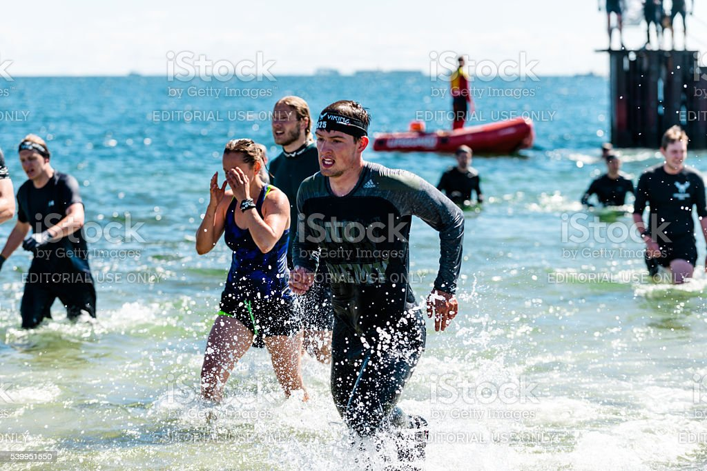 Obstacle course at sea with runners in water knee deep stock photo