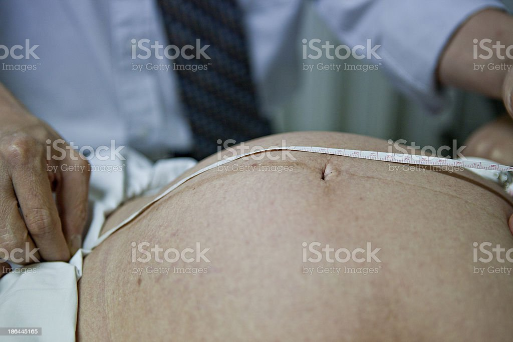 Obstetrician examining pregnant belly by ultrasonic scan. stock photo