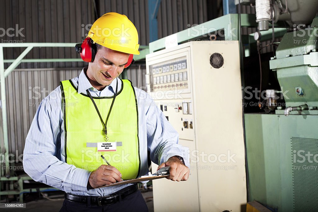 Occupational health and safety officer in factory stock photo