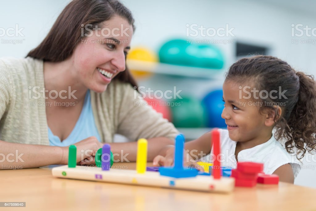 Occupational therapist working with young African American girl at table stock photo