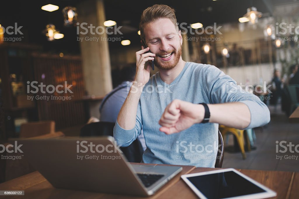 Occupied businessman multitasking in cafe stock photo