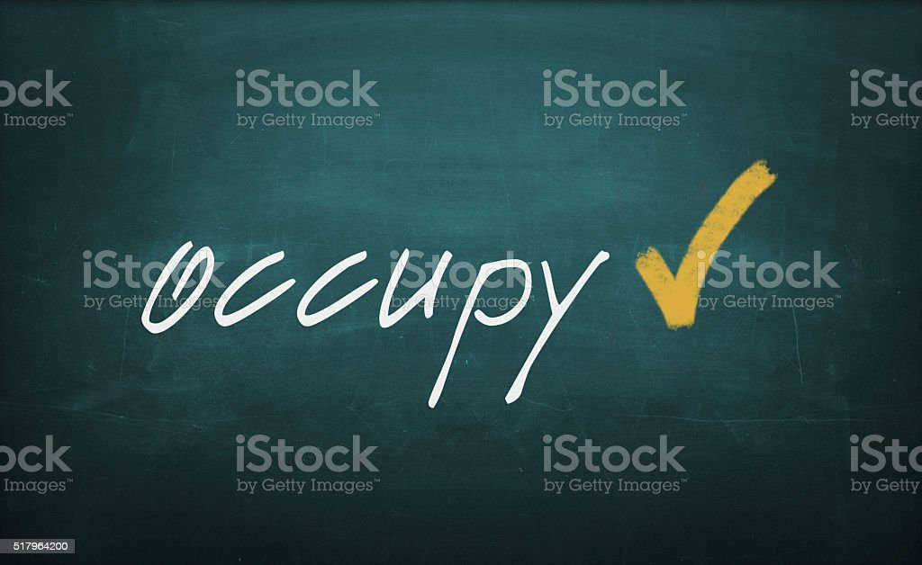 Occupy Text Written with Chalk on a Dirty Blackboard stock photo