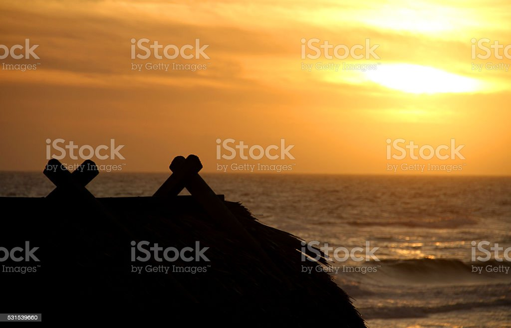 Ocean and sunset with roof of a house stock photo