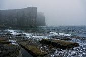 Ocean cliffs in heavy fog