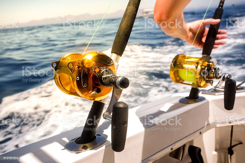 Ocean Fishing Reels and Rods with Grabbing Hand stock photo