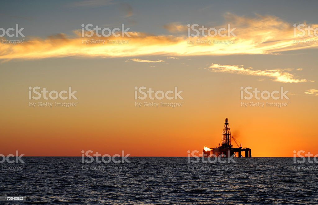 Ocean oil rig silhouette at sunset. stock photo
