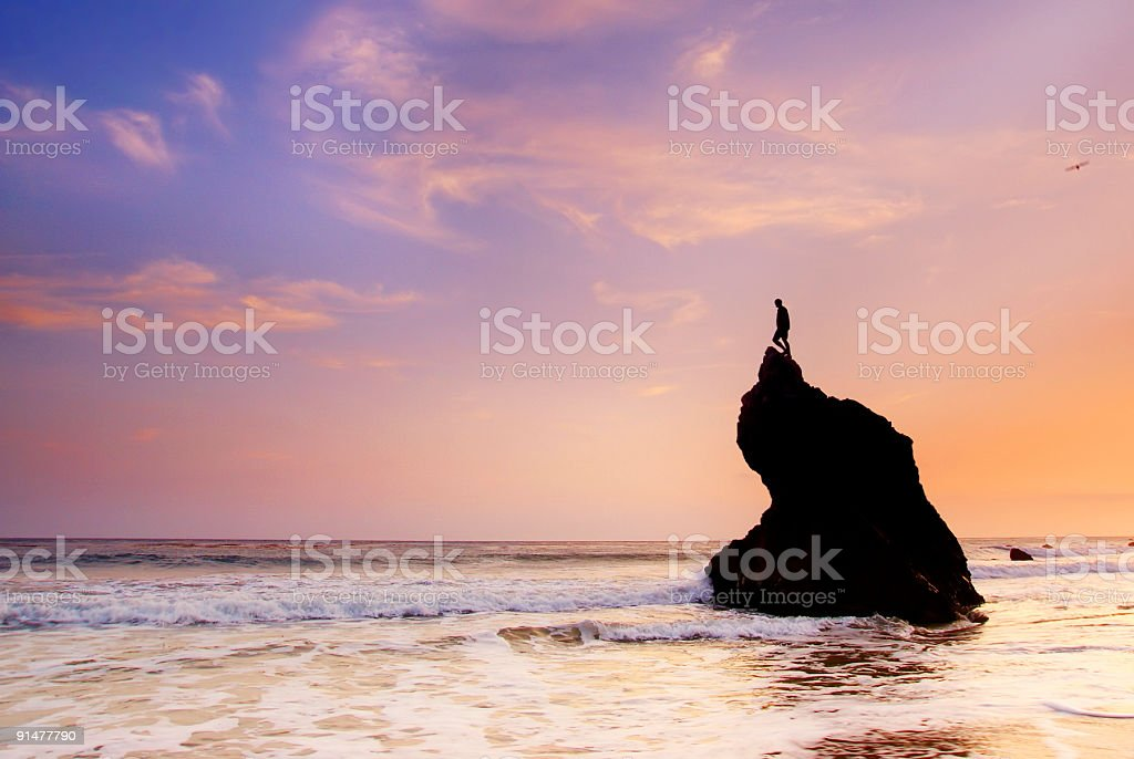 ocean sky sunset and man on top of rock formation royalty-free stock photo