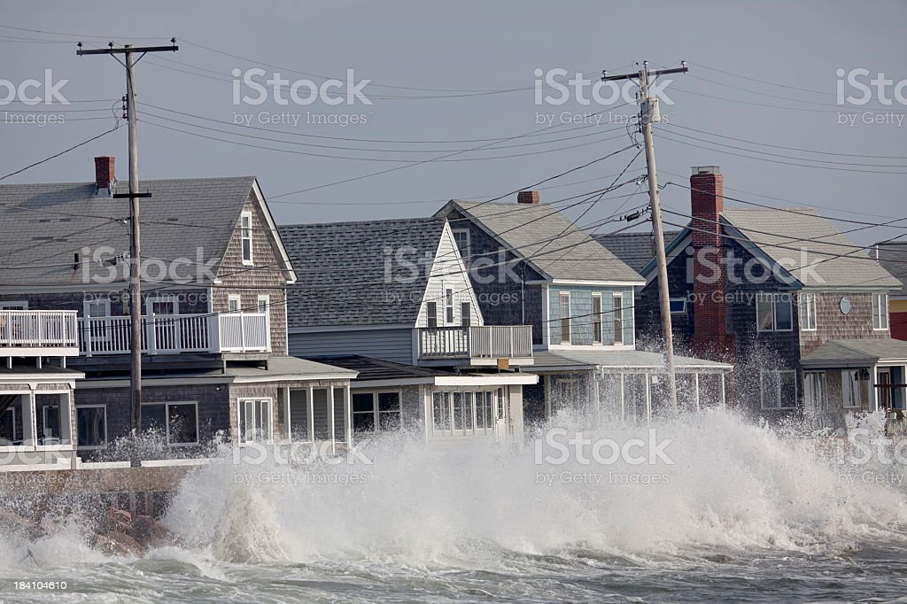Ocean Storm Waves Crashing into Seawall in front of Houses stock photo
