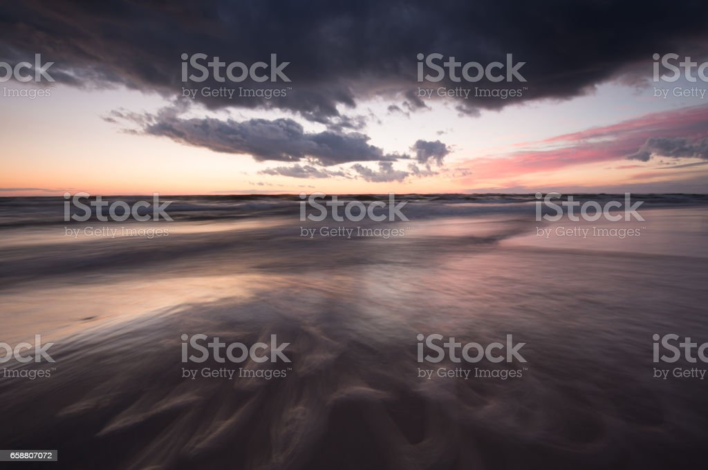 Ocean sunset scene with waves photographed with long exposure stock photo