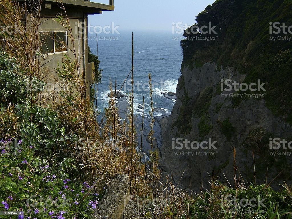 Ocean, volcanic cliffs, cabin and shore stock photo