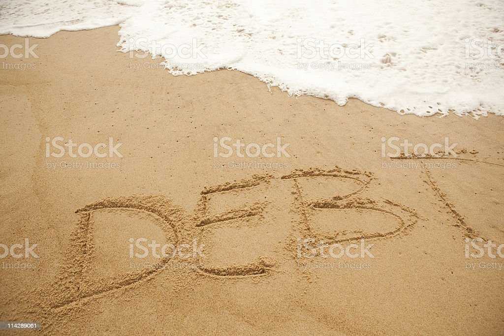 Ocean wave washing away word DEBT stock photo