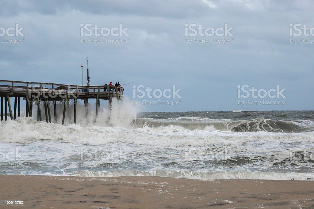Ocean Waves Fron a Nor'easter Crashing Into Fishing Pier stock photo