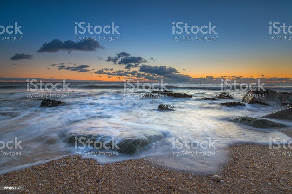 Ocean waves rushing over rocks stock photo