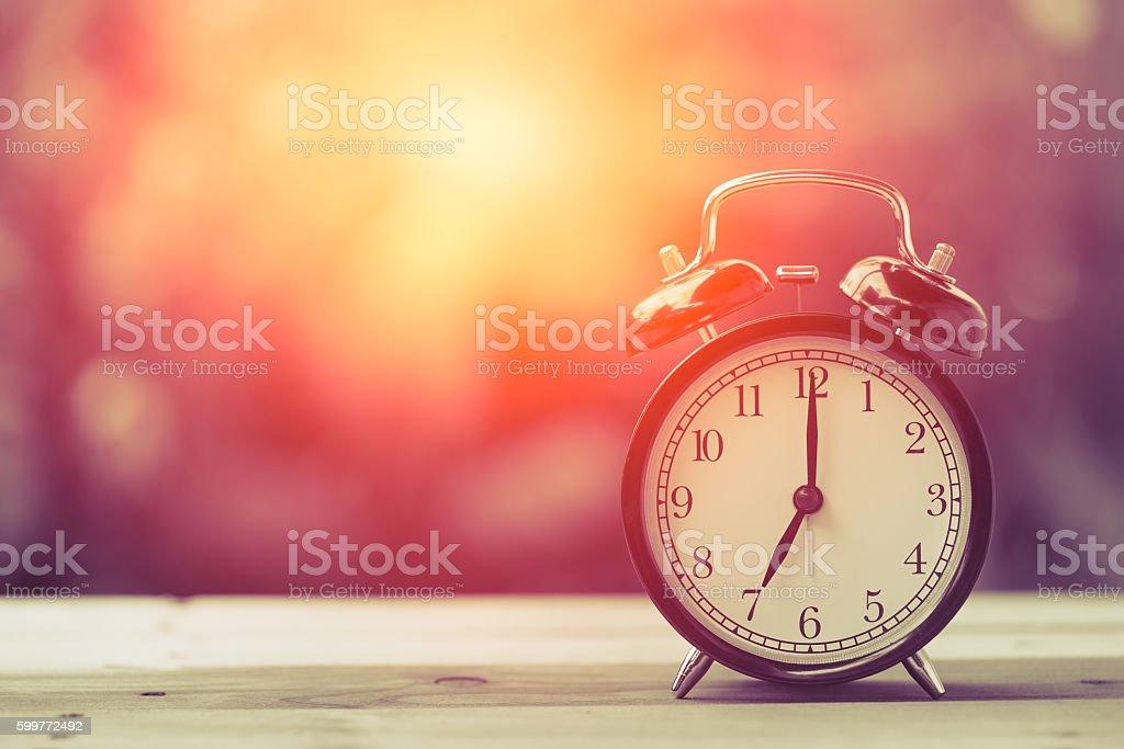 7 o'clock Clock Vintage on Wood Table with Sun Light stock photo
