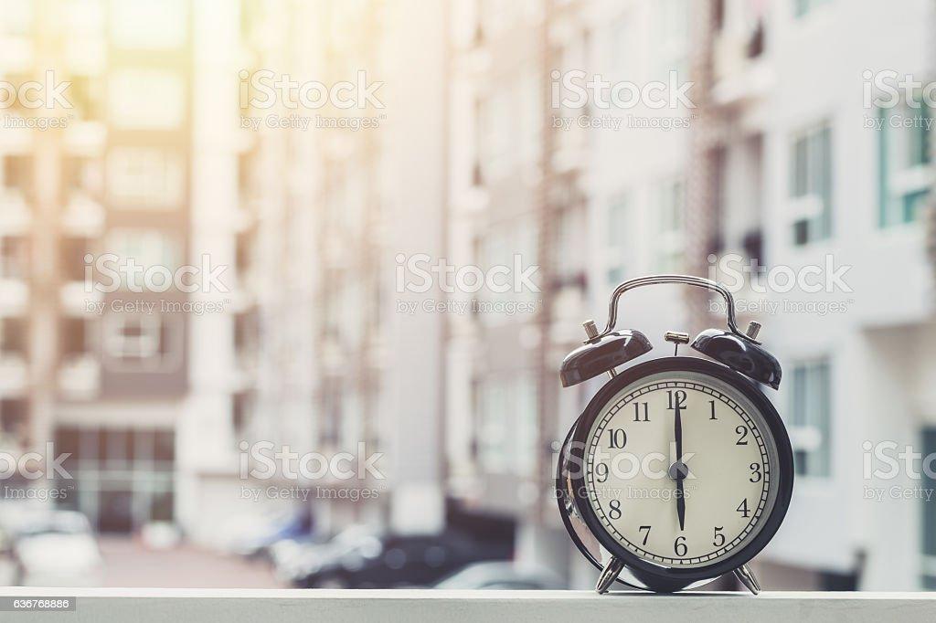 6 o'clock retro clock with The Clock condominium background. stock photo