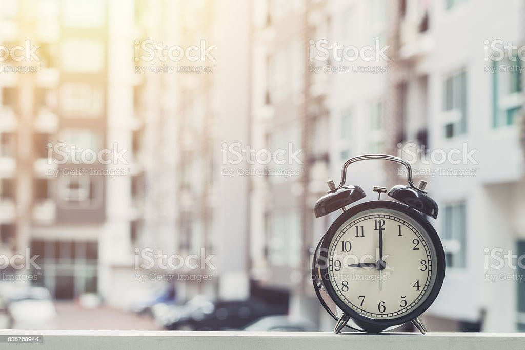 9 o'clock retro clock with The Clock condominium background. stock photo