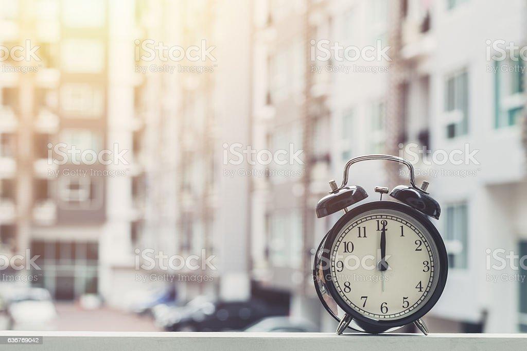 12 o'clock retro clock with The Clock condominium background. stock photo