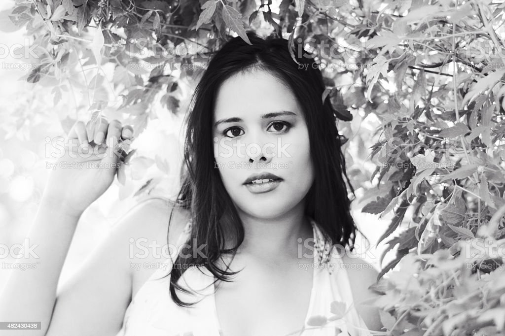 B&W of mixed race young woman under vine archway. stock photo