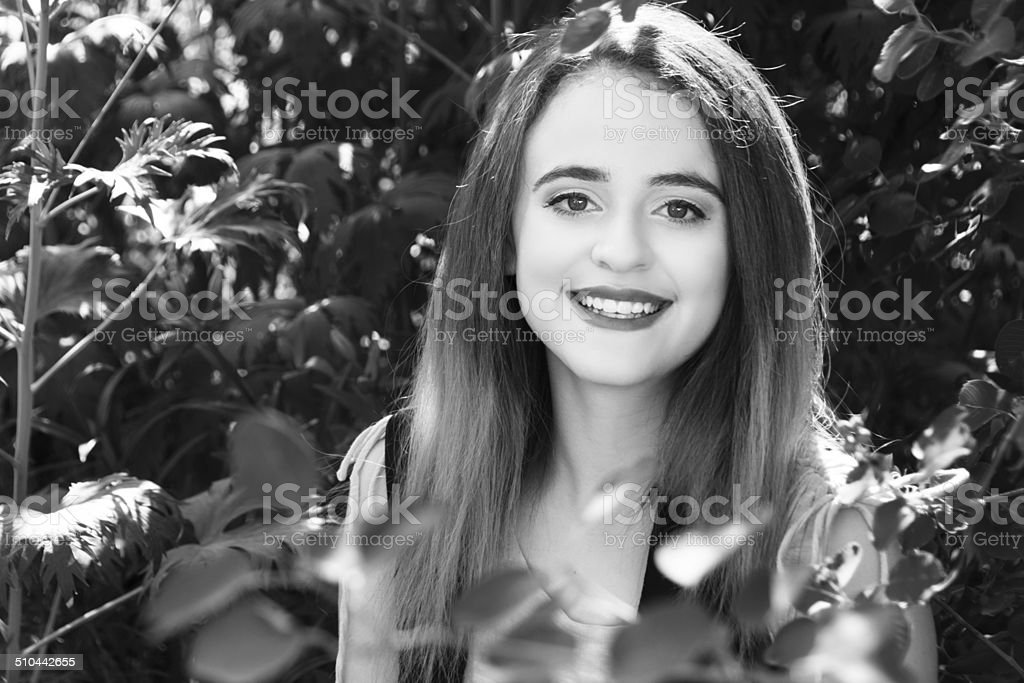 B&W of smiling 15 year old girl in garden. stock photo