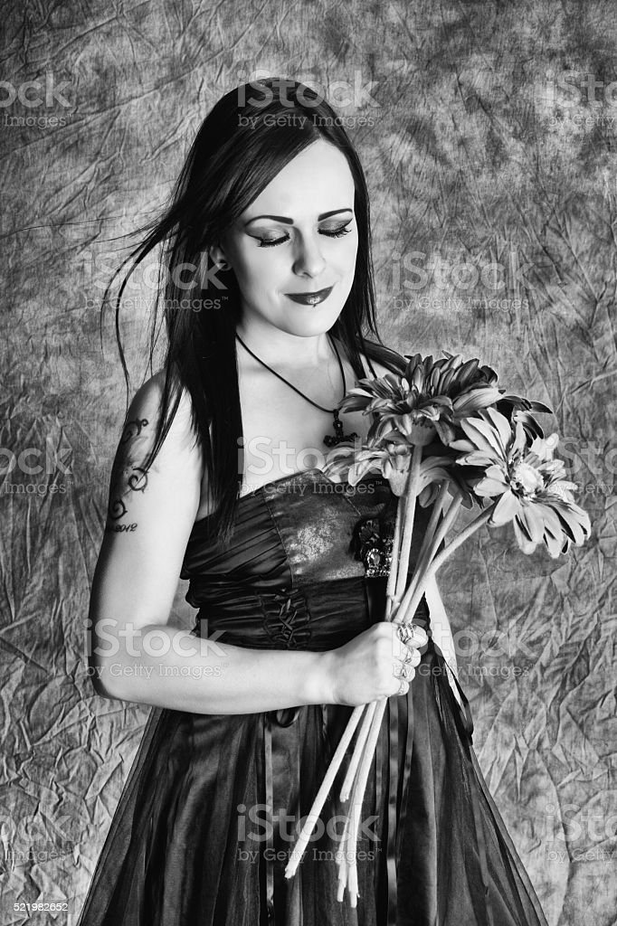 B&W of young woman smiling with flowers. stock photo