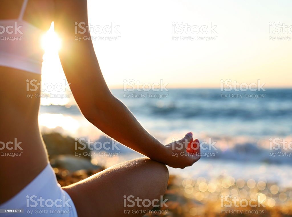 Off center view of a young woman meditating on the beach royalty-free stock photo