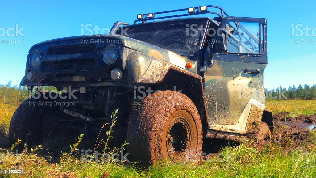Off road vehicle coming out of a mud hole hazard stock photo
