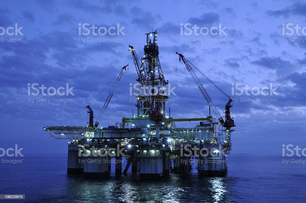 Off Shore Drilling Platform at Twilight. Oil rig and reflection stock photo