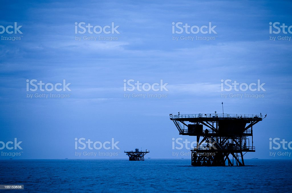 Off shore oil platforms at dusk royalty-free stock photo