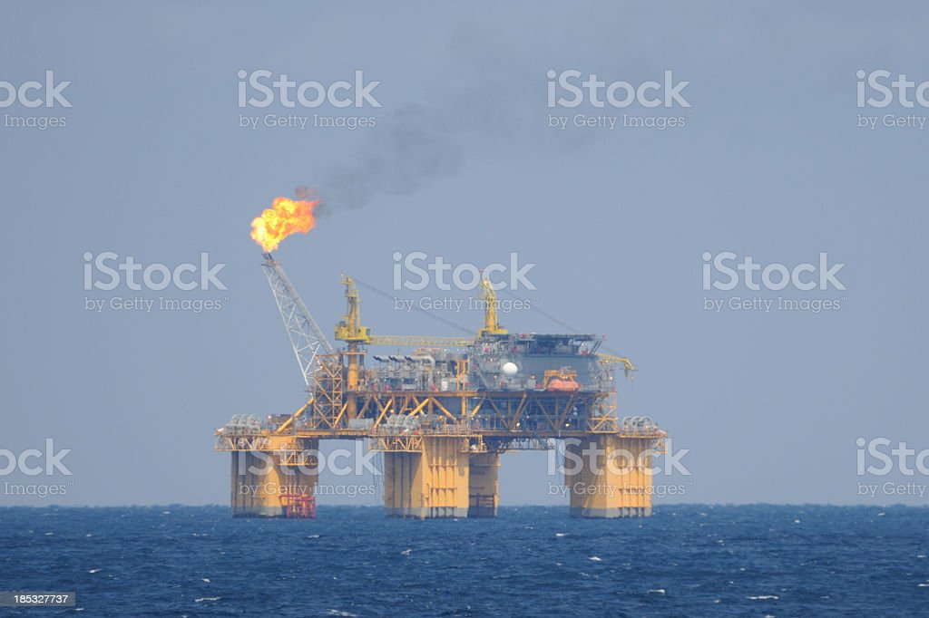 Off shore oil production platform with flare stack stock photo