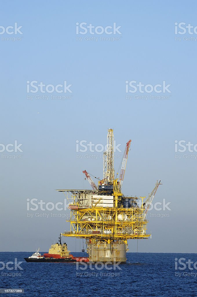 Off shore production platform with supply vessels. Oil rig stock photo