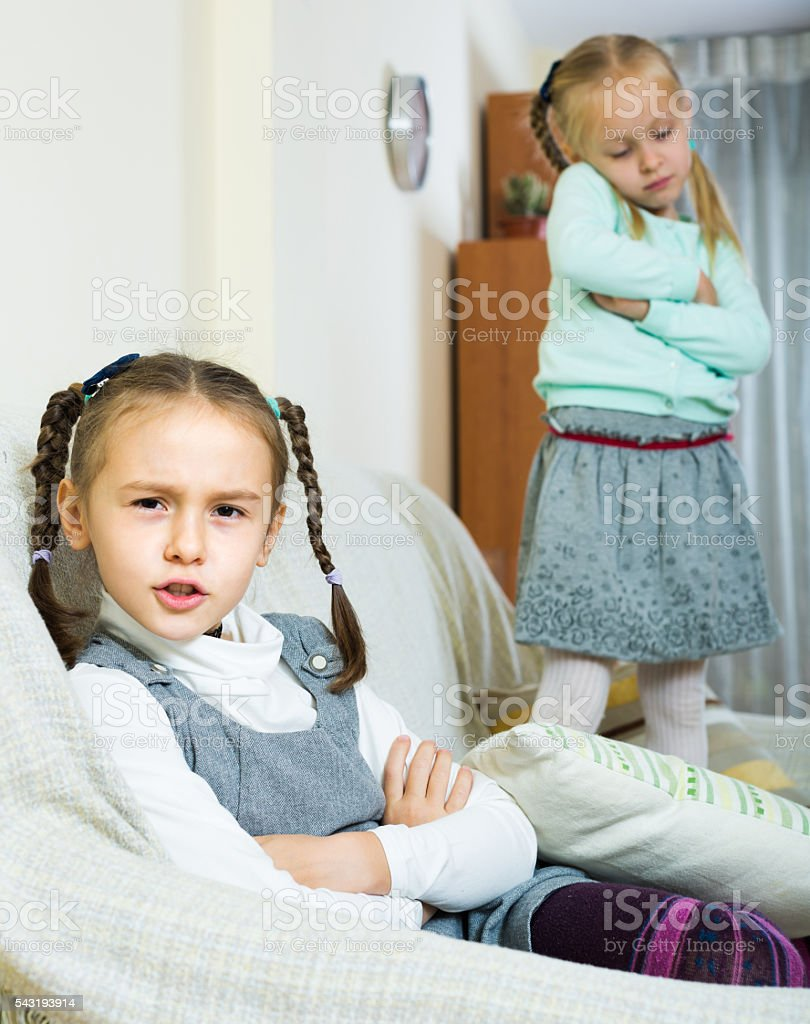 Offended girls sitting apart at home stock photo