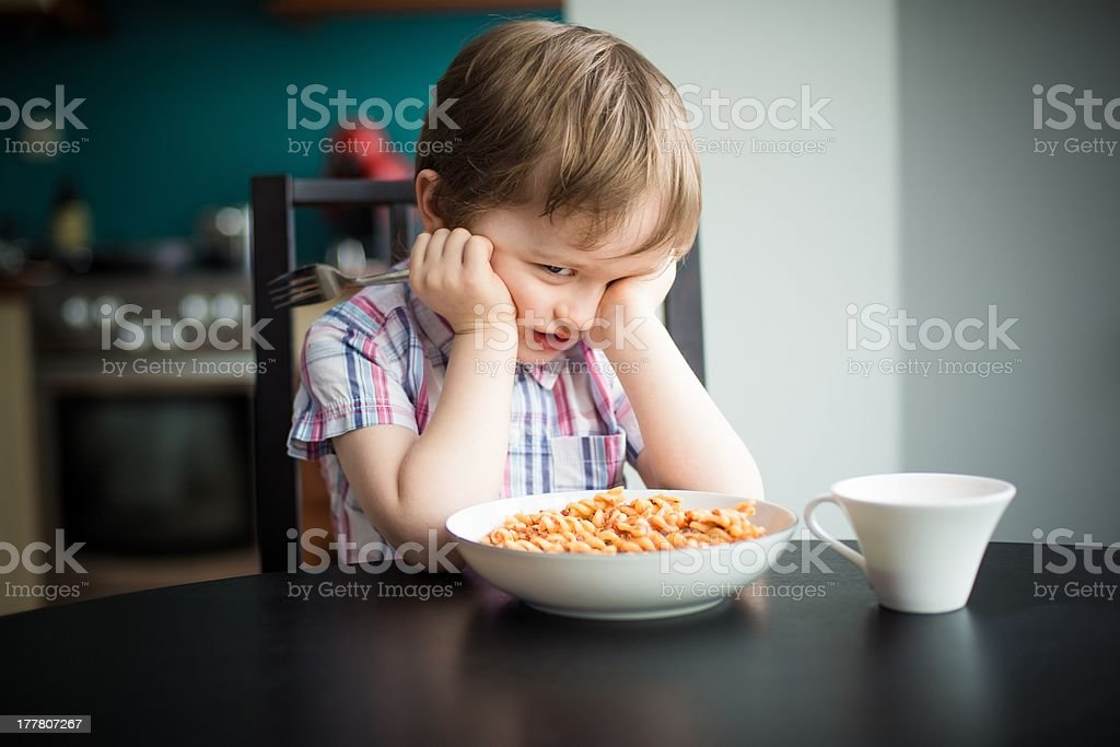 Offended little boy refuses to eat dinner stock photo