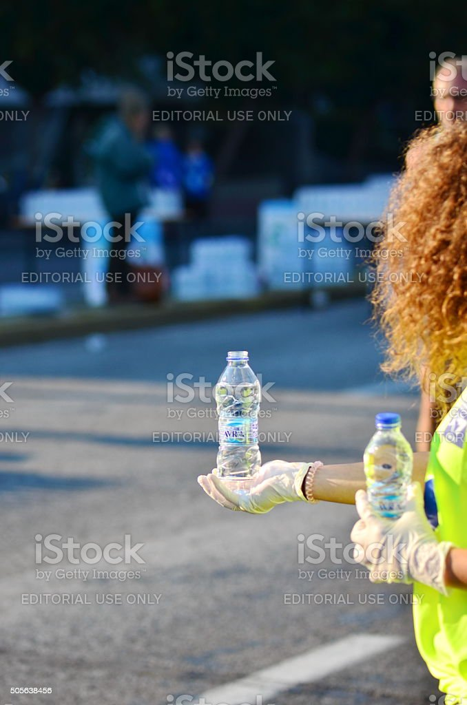 Offering a bottle of water to a runner stock photo