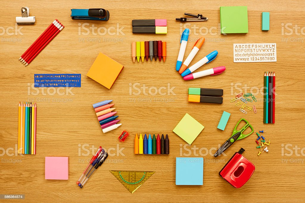 Office and school supplies are arranged on wooden table stock photo