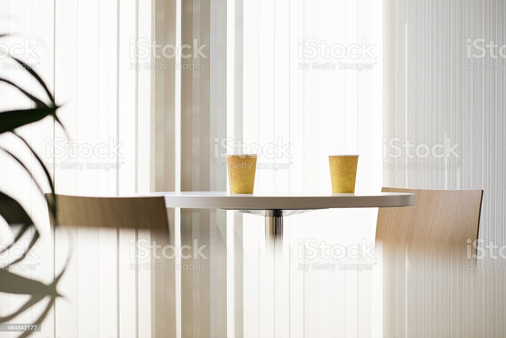 Office break room with modern tall table and bar stools. The table...