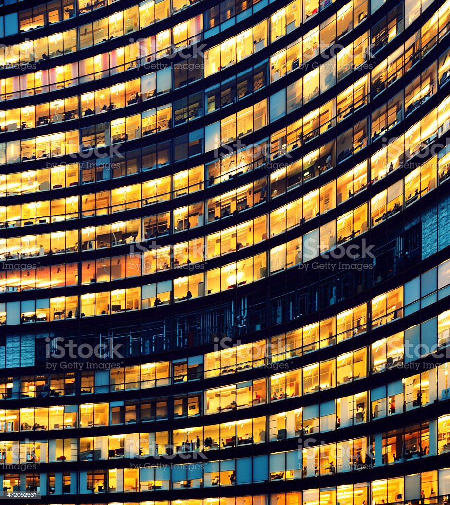 Office building at night with illuminated windows stock photo