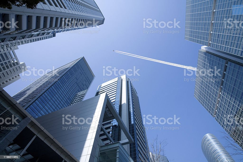 Office Buildings and plane with a contrail royalty-free stock photo