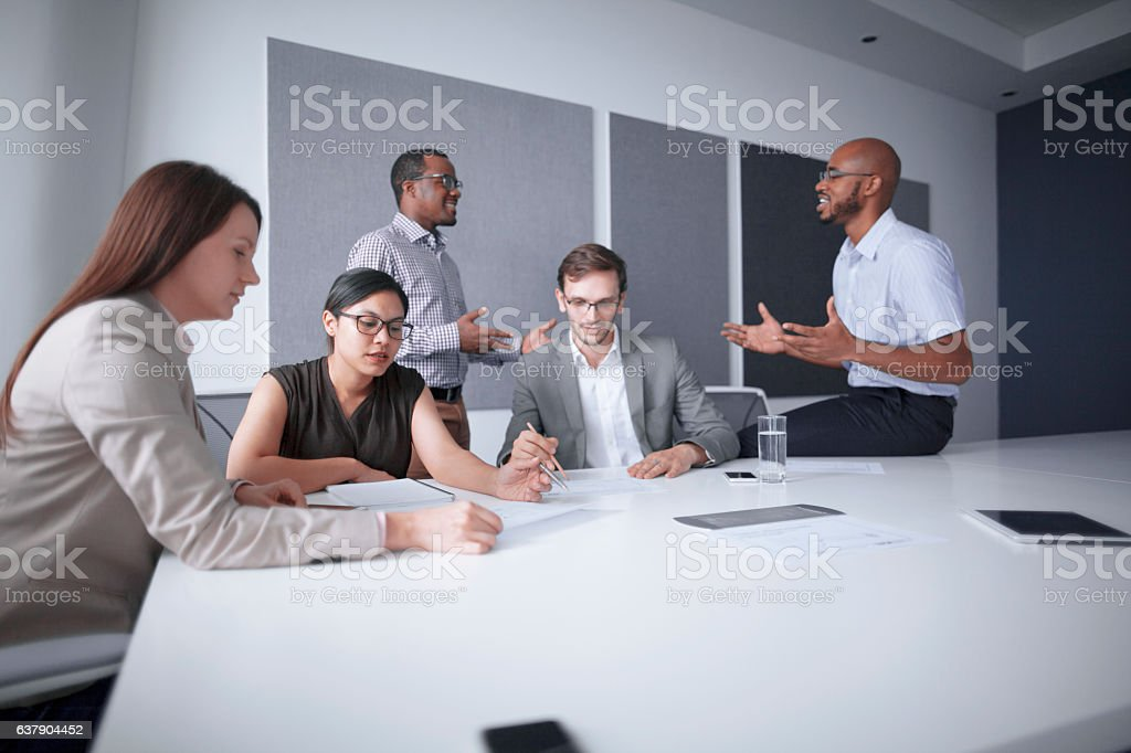 Office colleagues conversing in business meeting stock photo