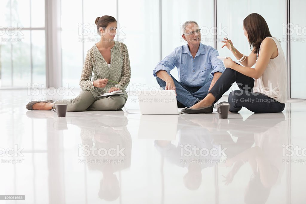Office colleagues in discussion while sitting on floor royalty-free stock photo