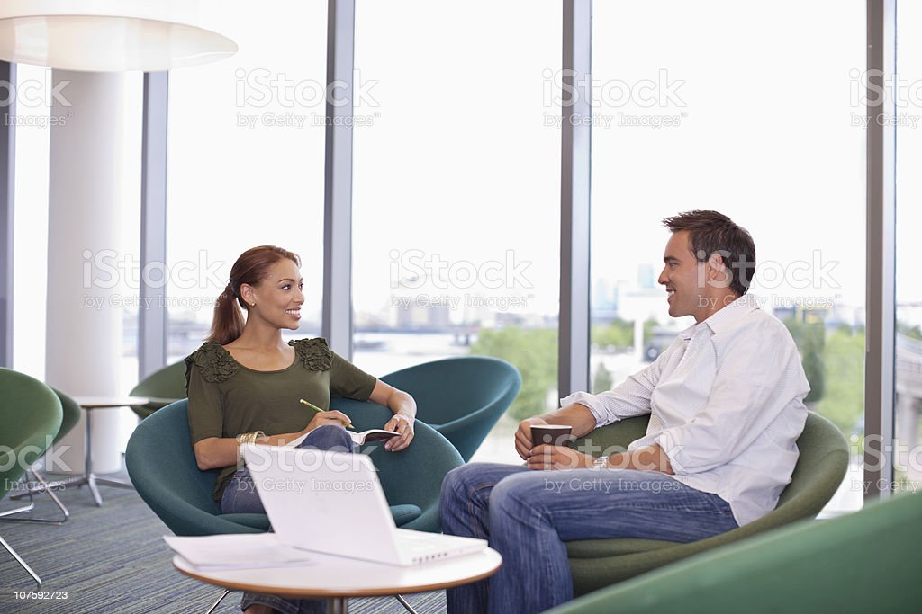 Office colleagues sitting at office canteen during coffee break with laptop royalty-free stock photo