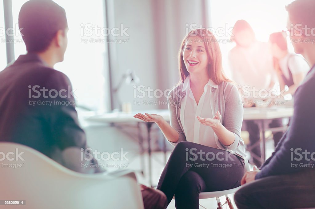 Office coworkers talking during meeting together in design studio stock photo