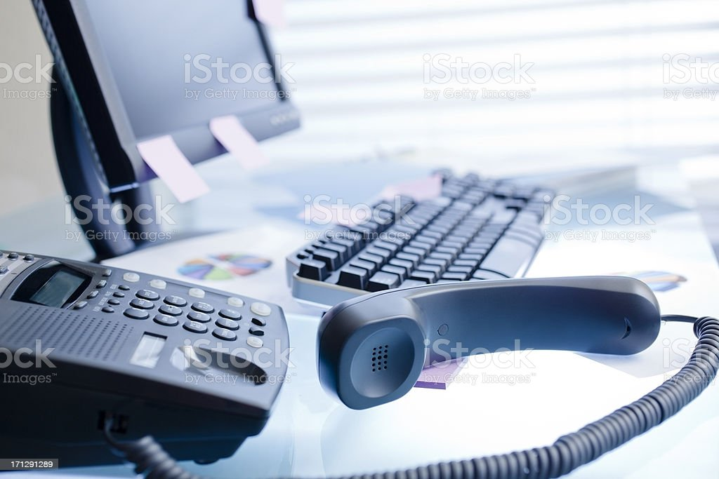 Office desk, graphs, charts by window. Handset off the hook. stock photo