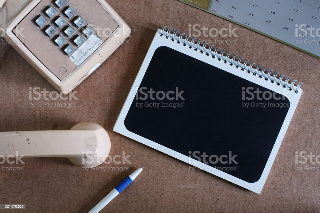 Office desk table with notepade and telephone.Top view stock photo