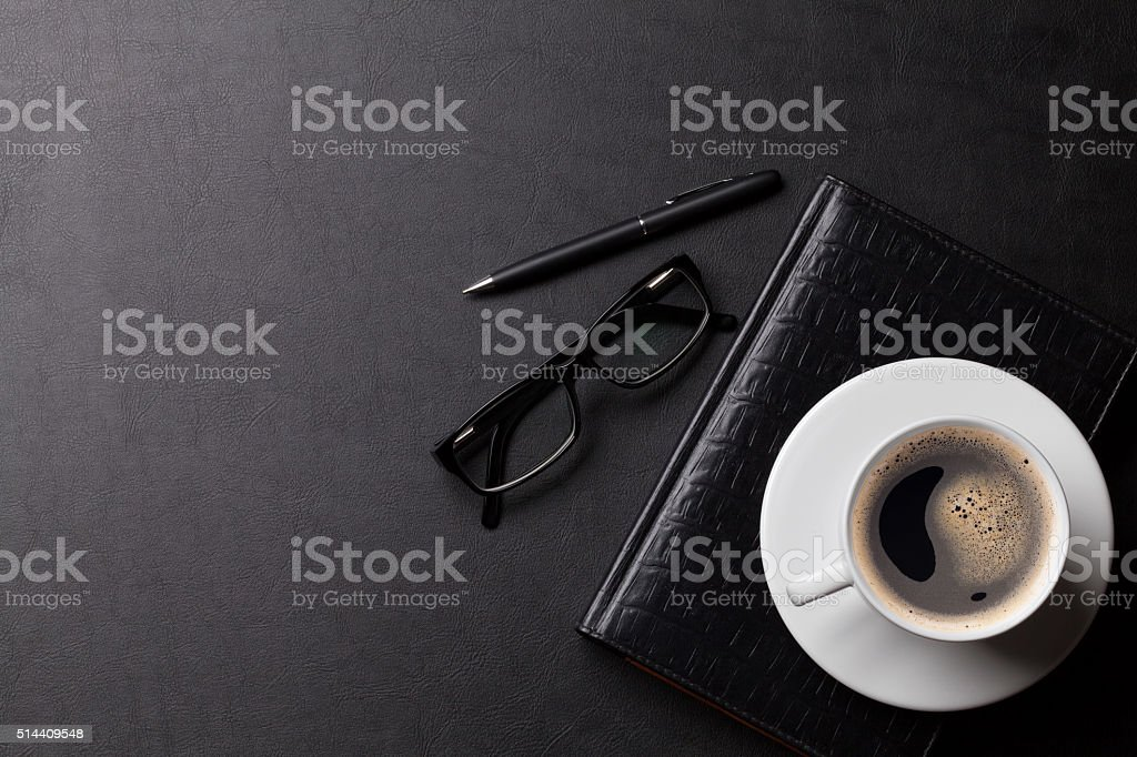 Office desk with coffee, glasses and supplies stock photo