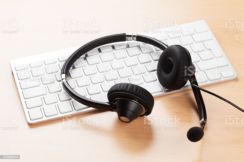 Office desk with headset and keyboard stock photo