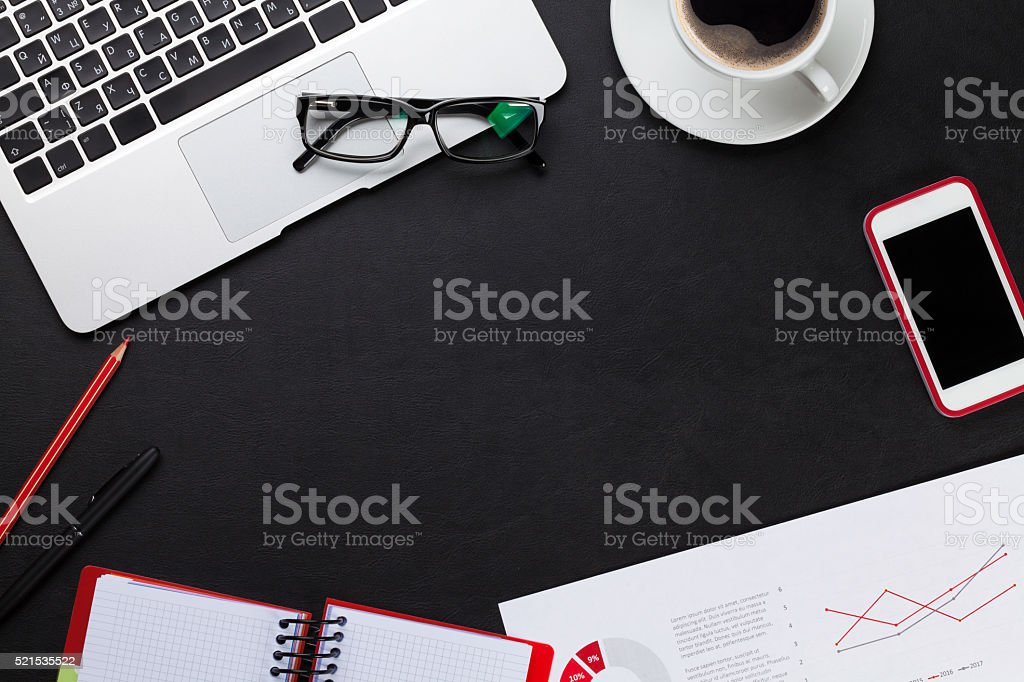 Office desk with laptop, coffee, notepad and phone stock photo