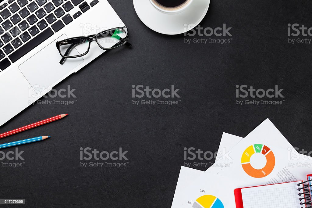Office desk with laptop, coffee, notepad and reports stock photo